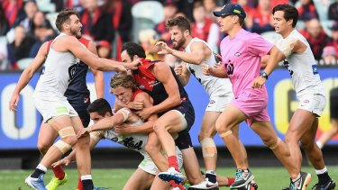 Carlton and Melbourne players wrestle during their round two match at the MCG.