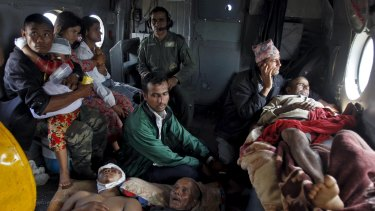 Victims of Saturday's earthquake rest inside an Indian Air Force helicopter as they are evacuated from Trishuli Bazar to the airport in Kathmandu, Nepal.