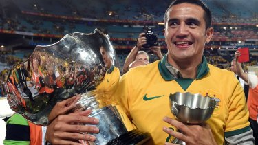 Tim Cahill, here holding the Asian Cup, is committed to playing in China for at least one season.