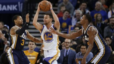 Golden State Warriors' Stephen Curry looks to get past Utah Jazz's Trey Burke (3) and Rodney Hood.