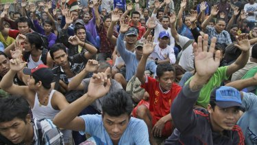 On April 3, rescued Burmese fishermen raise their hands as they are asked who among them wants to go home at the compound of Pusaka Benjina Resources fishing company in Benjina, Aru Islands, Indonesia.