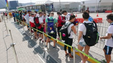 Swimmers wait for the athletes' bus after a training session.