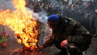A symbolic coffin of Russian President Vladimir Putin is set aflame by protesters in Odessa.