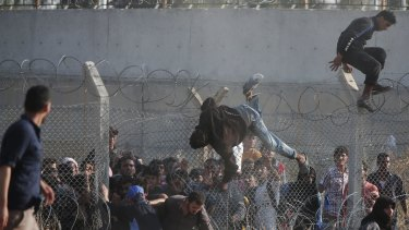 Desperate Syrian refugees cross into Turkey over and through a hole on the border fence.