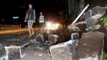 People walk past fallen walls in Mashiki.