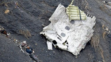 A rescue worker searches near a piece of fuselage among the debris at the crash site of an Airbus A320, near Seyne-les-Alpes.