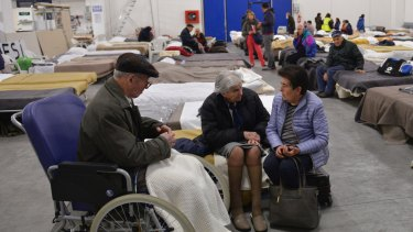 Elderly residents spend Sunday night in a shelter set in a warehouse in Caldarola, Italy.