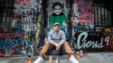 Luke Cornish in front of one of his portraits of a Syrian child.