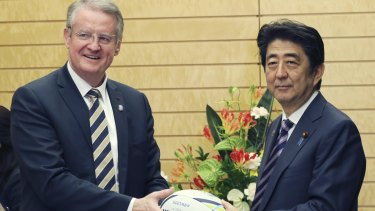 World Rugby chairman Bernard Lapasset presents a rugby ball to Japanese Prime Minister Shinzo Abe during a meeting in Tokyo on Monday.
