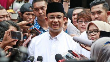 Anies Baswedan, centre, is mobbed by the press after casting his vote.