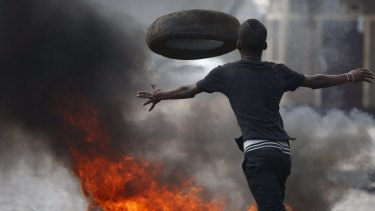 A protester hurls a tire on Tuesday at a protest against Burundi President Pierre Nkurunziza's bid for a third term.