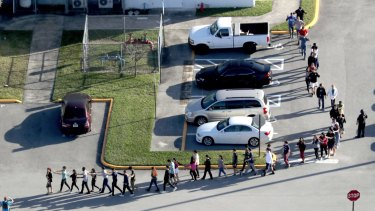 Students are evacuated by police from Marjory Stoneman Douglas High School in Parkland, Florida after the shootings.
