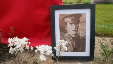A portrait of Lance-Corporal Vivian George Taylor rests against his gravestone as it awaits rededication at the Australian National Memorial in Villers-Bretonneux.