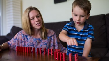 Rebecca O'Neil with son Connor , 5, counting dominos and learning to solve problems with building blocks.