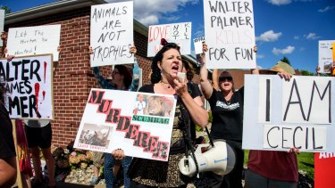 Rachel Augusta leads a group of protesters in front of Walter Palmer's dental practice.