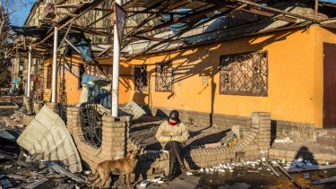 A woman sits on the remaining part of a wall of a damaged building in the central square.