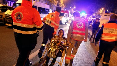 A person is evacuated after a shooting, outside the Bataclan Theatre in Paris.
