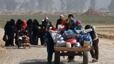 Iraqi civilians fleeing their homes due to fighting between government forces and IS on the western side of Mosul in March.