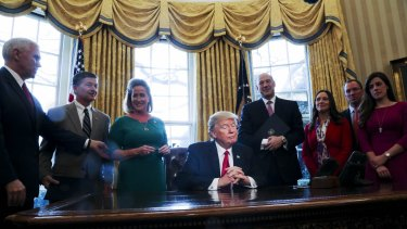 President Donald Trump in the Oval Office signing an executive order.