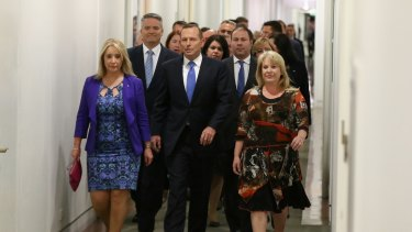Prime Minister Tony Abbott  arrives for a partyroom meeting on the leadership flanked by supporters.