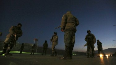 Afghan security forces stand guard near the site of two large bombings in Kabul on Tuesday.