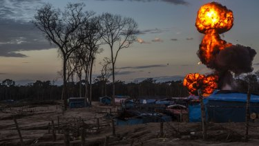 Flames rise into the sky at an illegal gold mining camp inside the Amazonian National Reserve.