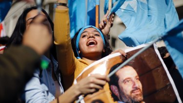 A girl chants slogans as she holds a picture of Lebanese Prime Minister Saad Hariri outside his residence in Beirut the day after his return.