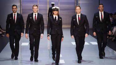 Qantas unveiled its new pilot uniforms on Friday. The female uniforms - pictured here alongside new male cabin crew outfits - are more tailored than the male look.