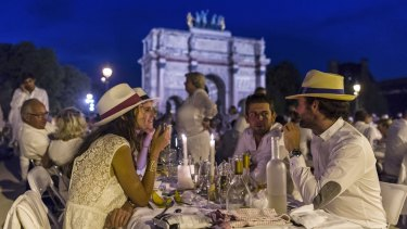 Participants dressed in white take part in Diner en Blanc, or White Dinner, backdropped by the Arc de Triomphe in Paris on Thursday.