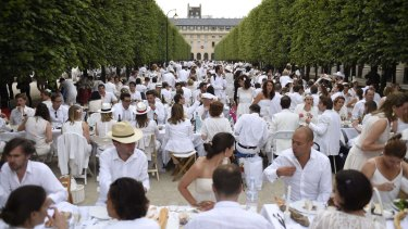Participants dressed in white enjoy their meal at the gardens of the Palais-Royal in Paris on Thursday.
