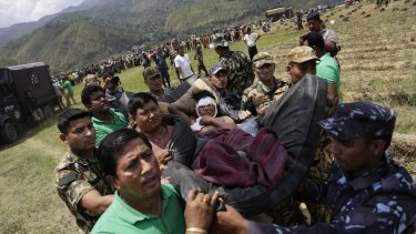 Nepalese soldiers carry a wounded man on a makeshift stretcher to a waiting Indian Air Force helicopter as they evacuate victims of Saturday's earthquake from Trishuli Bazar to Kathmandu airport in Nepal.