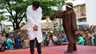 A man arrested for having gay sex is whipped in public for violating sharia law in ultra-conservative Aceh in May.