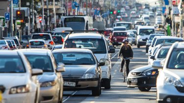 Trading parking and speed for safety, a cyclist rides on Sydney Road, Coburg.