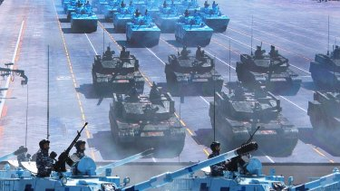 Chinese soldiers ride in tanks as they pass a large screen on Tiananmen Square.