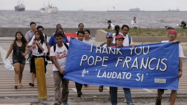 Environmental activists carry a banner as they march towards a Roman Catholic church to coincide with Pope Francis' encyclical on climate change on Thursday in Manila, Philippines.