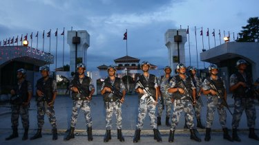 Nepalese policemen stand guard in front of the constituent assembly hall where a ceremony to adopt the country's new constitution was in progress in Kathmandu on Sunday.