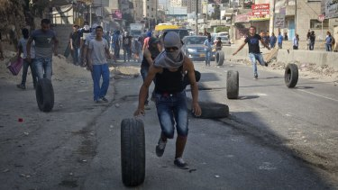 Palestinians roll tyres during clashes with Israeli troops at the Qalandia checkpoint between Jerusalem and the occupied West Bank city of Ramallah.