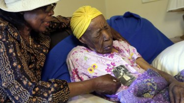 Lois Judge, left, holds a 1939 photo of her aunt Susannah Mushatt Jones, right, last year. Jones has died at the age of 116.