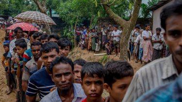 Rohingya men wait to collect building material for shelters at a refugee camp in Bangladesh.
