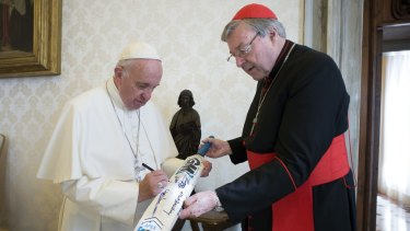 Pope Francis signs a cricket bat he received from Cardinal George Pell at the Vatican. Pell's dicky heart prevents him from fronting up to answer questions about abuse by Catholic church personnel.