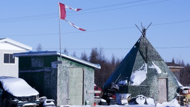 The remains of a Canadian flag fly over a building in Attawapiskat, a community plagued by suicides in Canada.