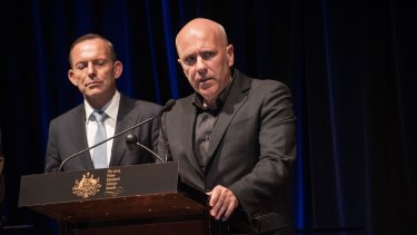 Prime Minister Tony Abbott, pictured in 2014, presenting Richard Flanagan with an award for The Narrow Road to the Deep North.