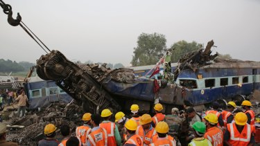 Rescuers search among the debris after 14 coaches of an overnight passenger train rolled off the track near Pukhrayan village in Uttar Pradesh state, India on Sunday.