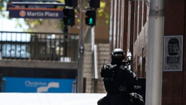 A police officer points his weapon towards the siege at Lindt Cafe in Martin Place