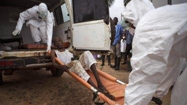 International effort: Health care workers assist a suspected Ebola sufferer in Sierra Leone.