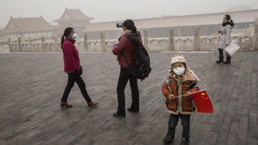 A Chinese boy  wears a mask as protection from the pollution as he stands with a China flag in the Forbidden City in Bejing on Tuesday.