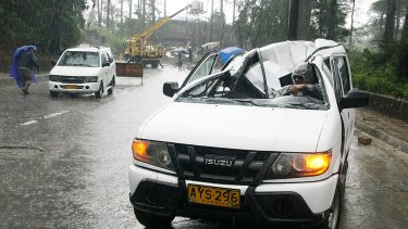A resident drives a vehicle damaged by a fallen electric post after Typhoon Goni battered Baguio city.