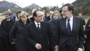 France's President Francois Hollande (centre), Spain's Prime Minister Mariano Rajoy (right) and German Chancellor Angela Merkel walk on a field near the crash site of Germanwings Airbus A320 near Seyne-les-Alpes.