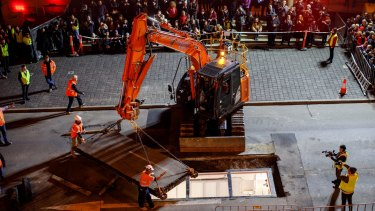 A crane closes over Parr's home for the next three days, as the crowd in Tasmania watches on.