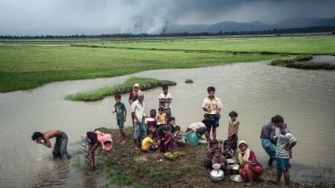 Rohingya refugees rest near the Naf River separating Myanmar and Bangladesh after crossing the border, as villages burns in the background.